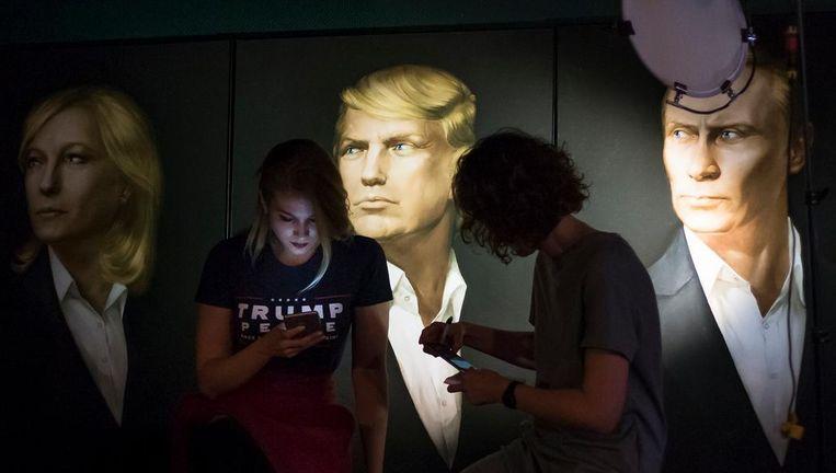 Twee vrouwen volgen de Amerikaanse verkiezingen in de Union Jack Pub in Moskou. Op de muur portretten van Le Pen, Trump en Poetin. Beeld AP