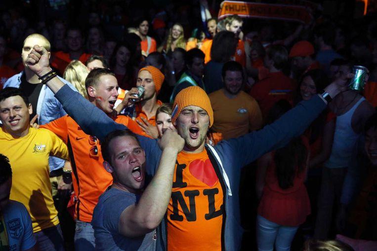 Australische en Nederlandse voetbalfans kijken samen in een bar naar de wedstrijd. Beeld anp