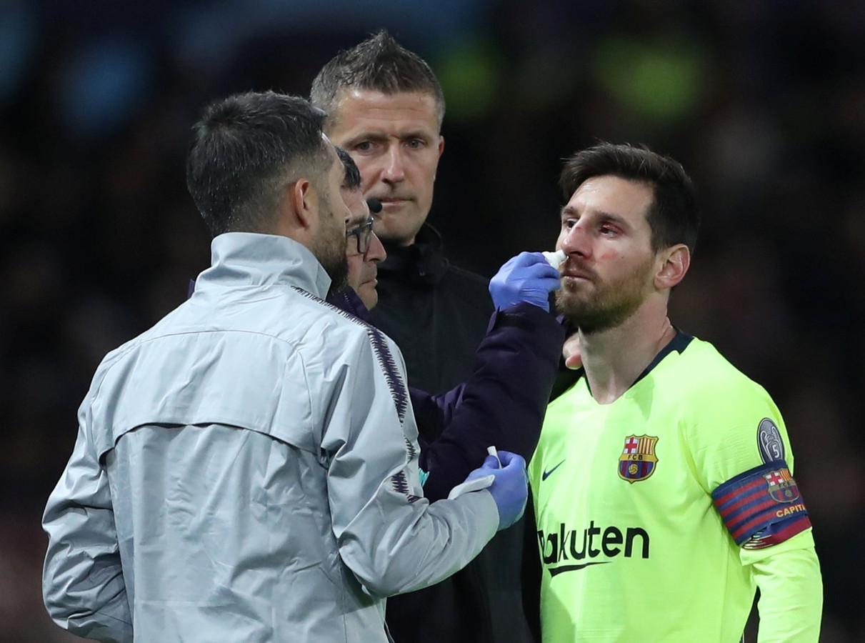 Lionel Messi wordt behandeld na zijn botsing met Chris Smalling.