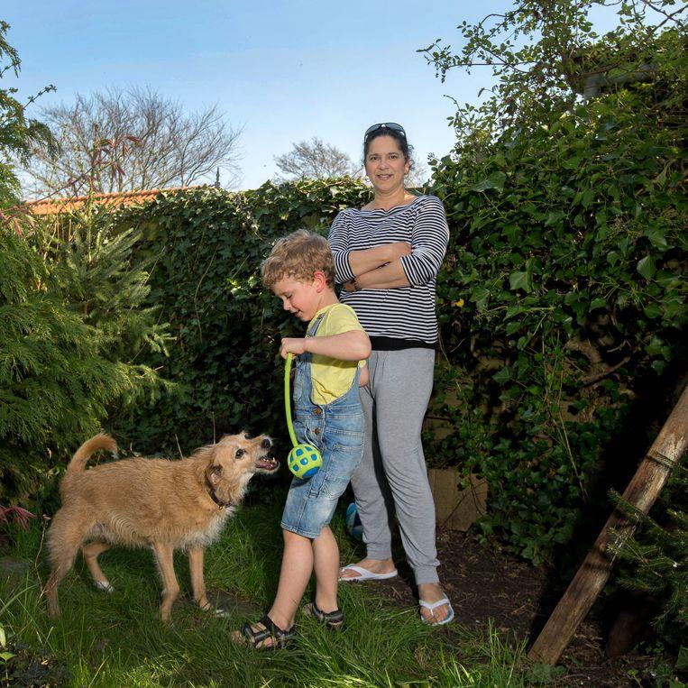Melany Brunings met haar zoon en hond in de tuin in Lutjewinkel. Beeld Maartje Geels