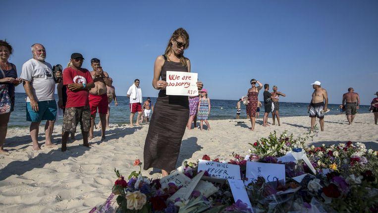 Een vrouw legt zondag in Sousse een tekst bij de plaats waar vrijdag 38 doden en 39 gewonden vielen toen een schutter het vuur opende. Beeld Zohra Bensemra / Reuters