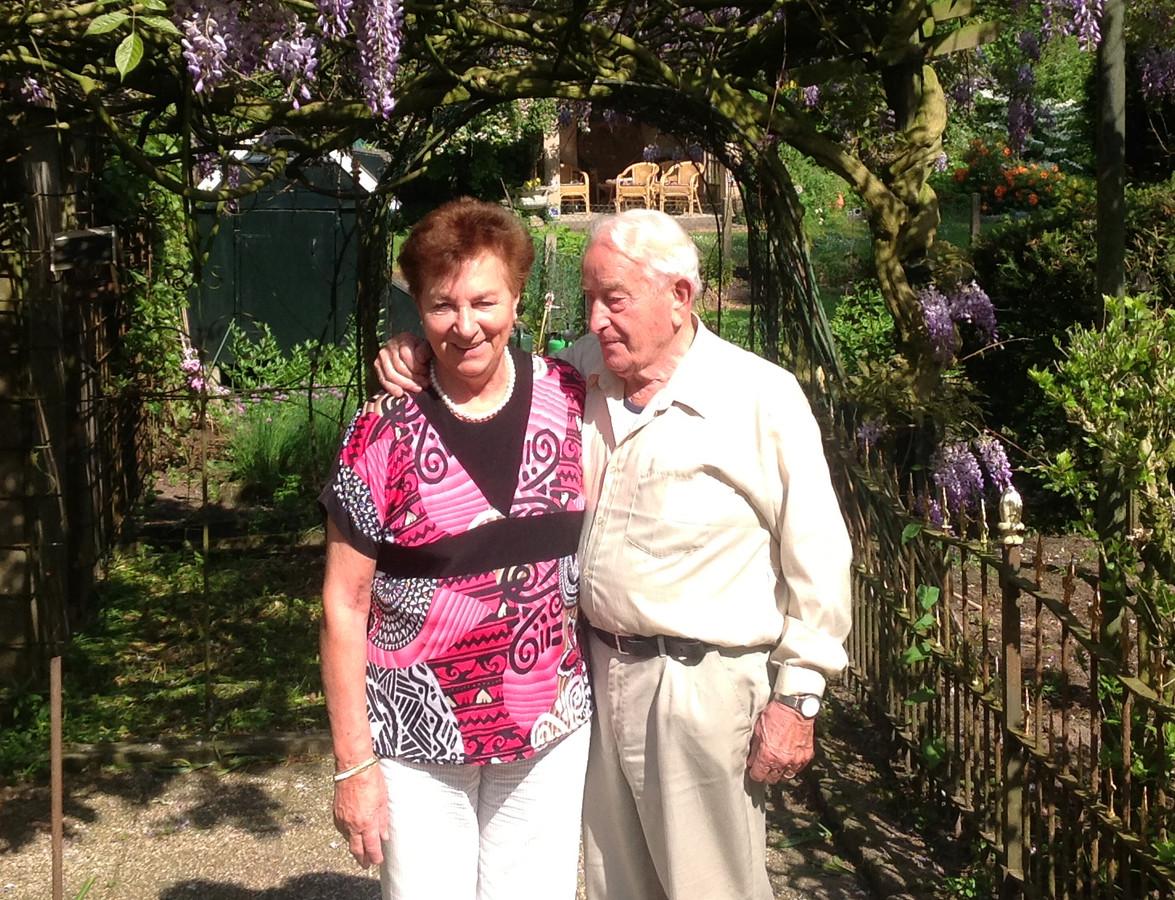 Jos en Sam van Rooijen in hun tuin aan de Stationsweg, met de bloeiende blauwe regen.