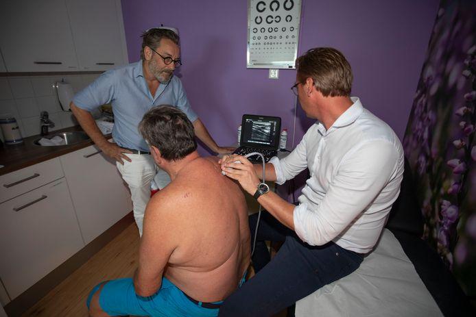 Huisarts Rob Roelofsen (links) en radioloog Bob Looij buigen zich over een patiënt. De scan wijst uit dat hij een vetbultje moet laten weghalen op zijn rug.