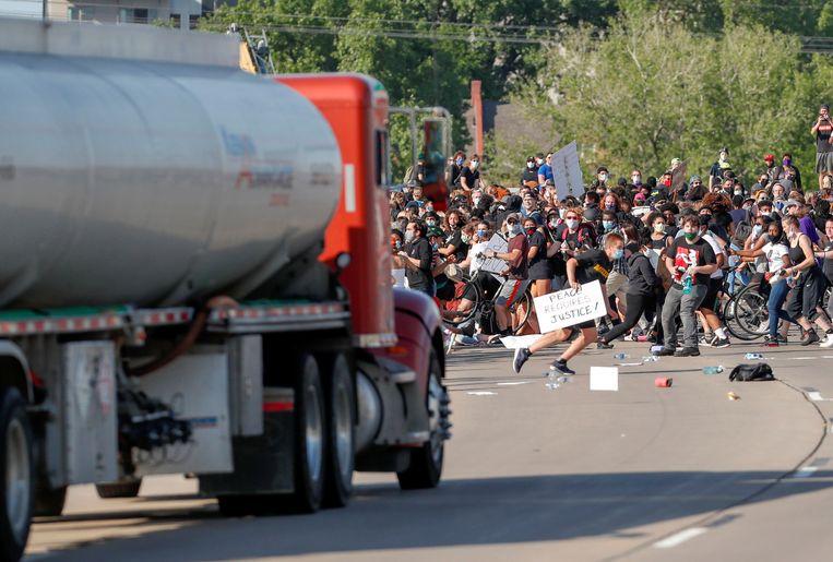 Een truck rijdt in op duizenden demonstranten in Minneapolis. Beeld REUTERS