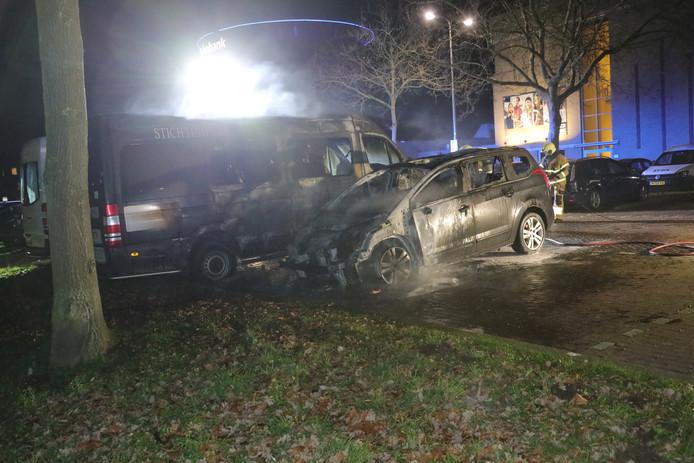 De in brand gestoken auto in Oss vlak voor kerst, met ernaast de rolstoelbus van de Vrienden van Norbertus uit Gennep.