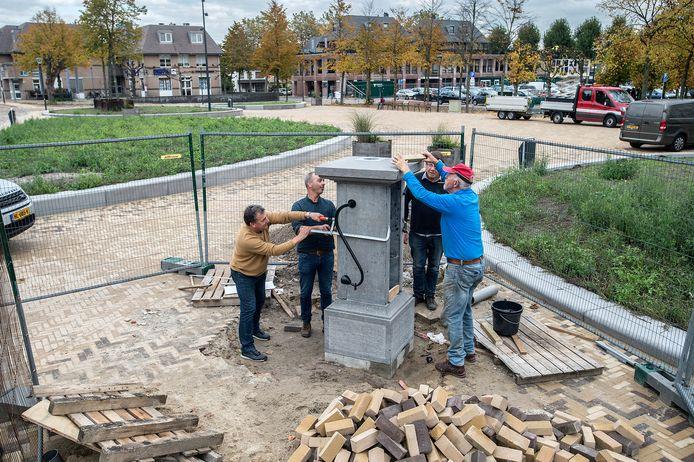 De herinrichting van de Markt is bijna afgerond. Henk Schoot (geheel rechts) en andere leden van CV De Zwoertjes hebben ook de waterpomp weer teruggeplaatst.