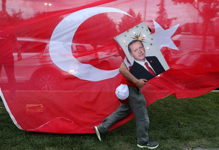 Een aanhanger van president Erdogan loopt met zijn portret voor een Turkse vlag langs.