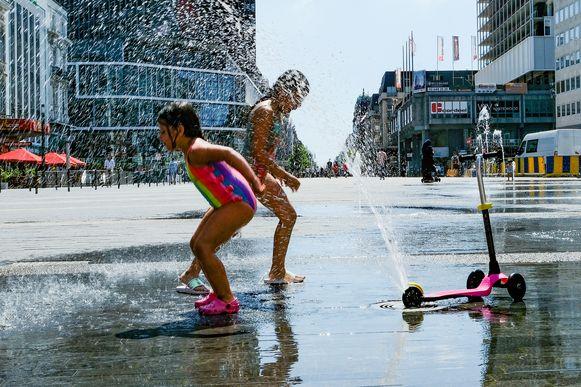 Kinderen zoeken verkoeling aan de fonteinen op het De Brouckèreplein.
