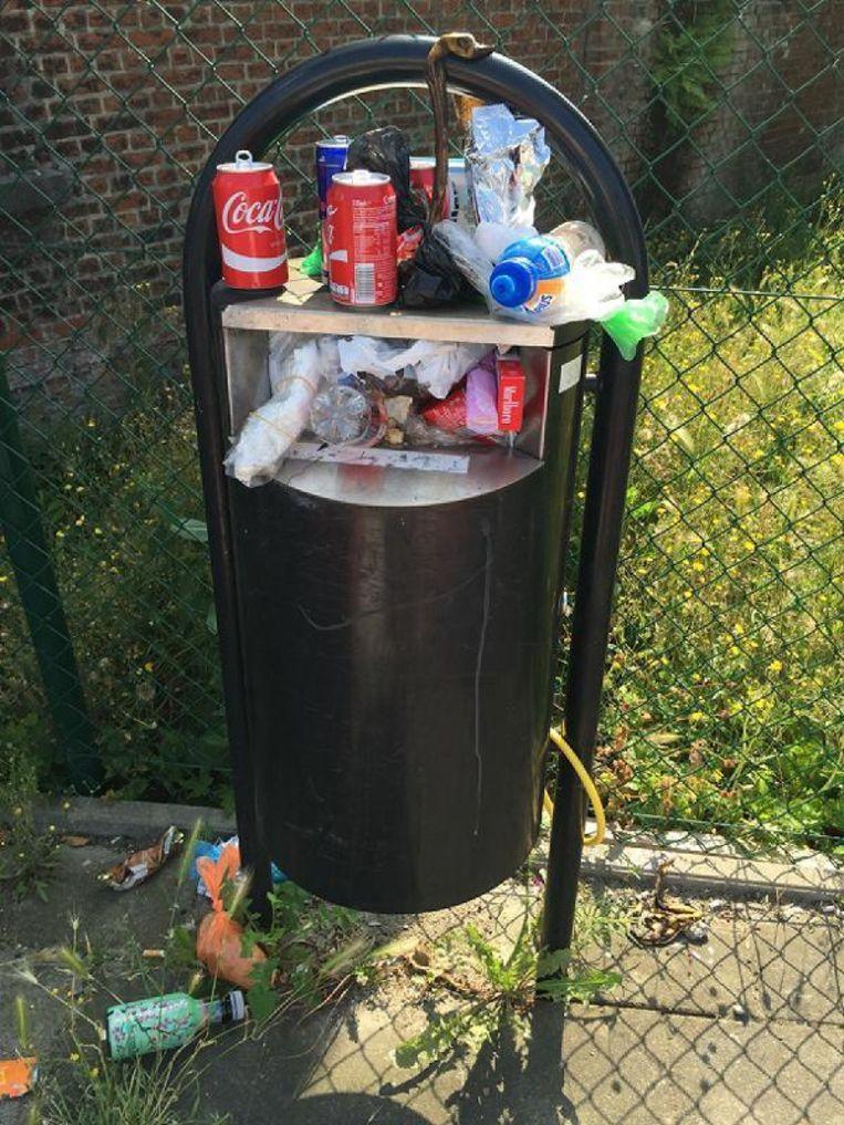 Een overvolle openbare vuilnisbak aan een bushalte.