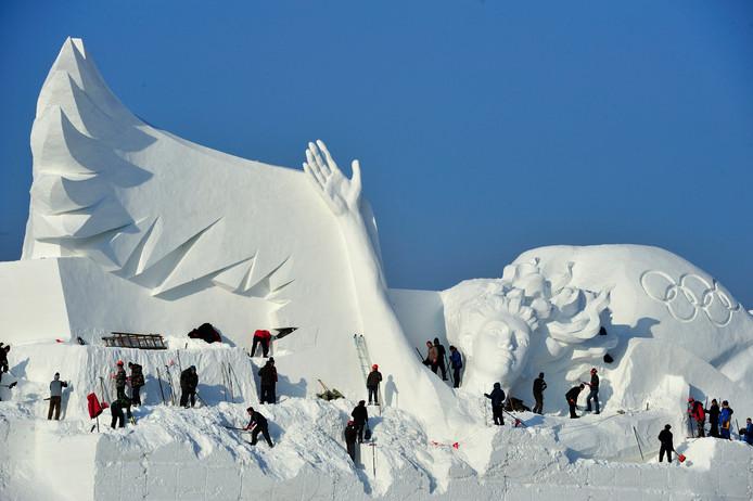 Medewerkers van het jaarlijkse Sneeuwfestival in de Chinese plaats Harbin zijn bezig om de sculpturen voor de opening van 20 december klaar te krijgen. Foto Tao Zhang