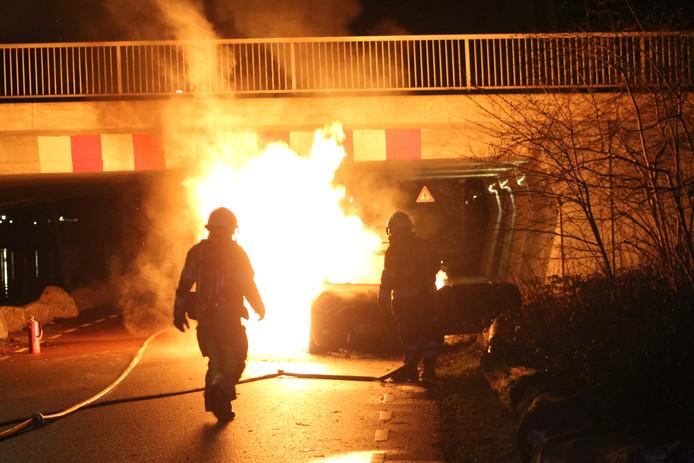 Brandweerlieden bij de brandende auto aan de Vechtdijk.