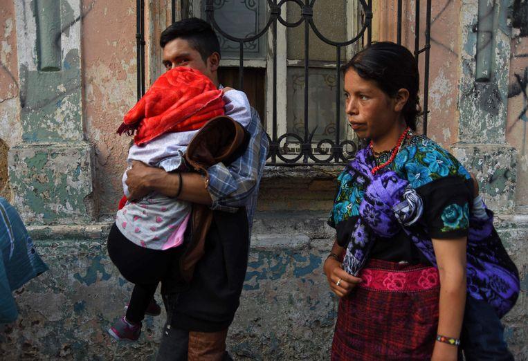 Nazario Jacinto draagt zijn 5-jarige dochter in Guatemala Stad. Het kind was van haar familie gescheiden toen zij illegaal de Amerikaanse grens waren overgestoken.  Beeld AFP