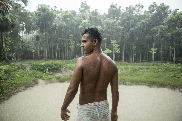 Man in de moessonregen in Jessore, Bangladesh. Beeld Mike Roelofs