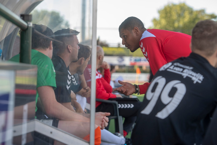 """Achilles Veen-trainer Giovanni Franken (rechts, in het rood) geeft uitleg aan zijn wisselspelers. ,,Er staat hier een talentvolle groep"""", vindt de nieuwkomer."""