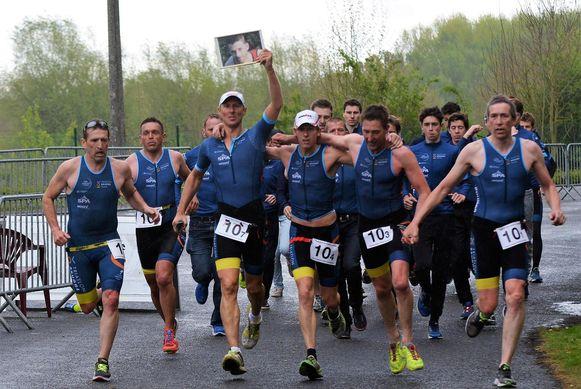 Met een foto van Kenneth Neyt in de hand lopen de triatleten van het Brugse team hun BK.