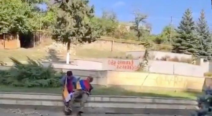 Beeld uit de executievideo.  De twee Armeniërs hebben de Armeense vlag en de vlag van de Republiek Artsach rond zich. Vermoedelijk zijn ze hier nog in leven.