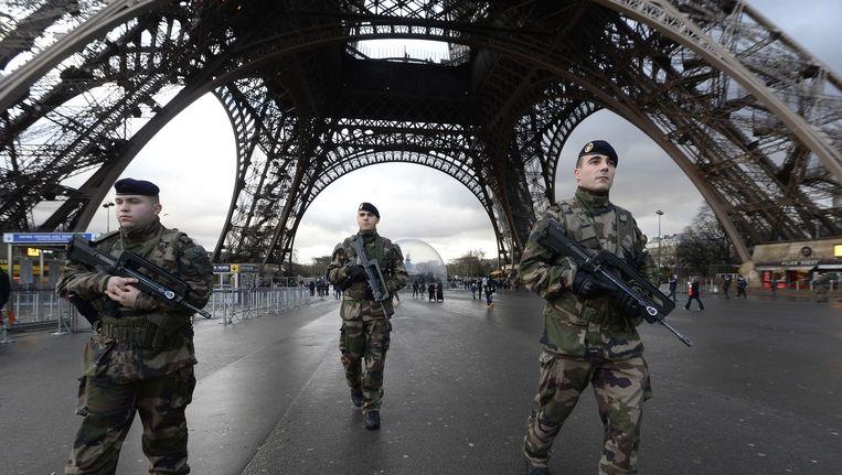 Militairen bij de Eiffeltoren na de aanslagen op de redactie van Charlie Hebdo en een Joodse supermarkt. Beeld AFP