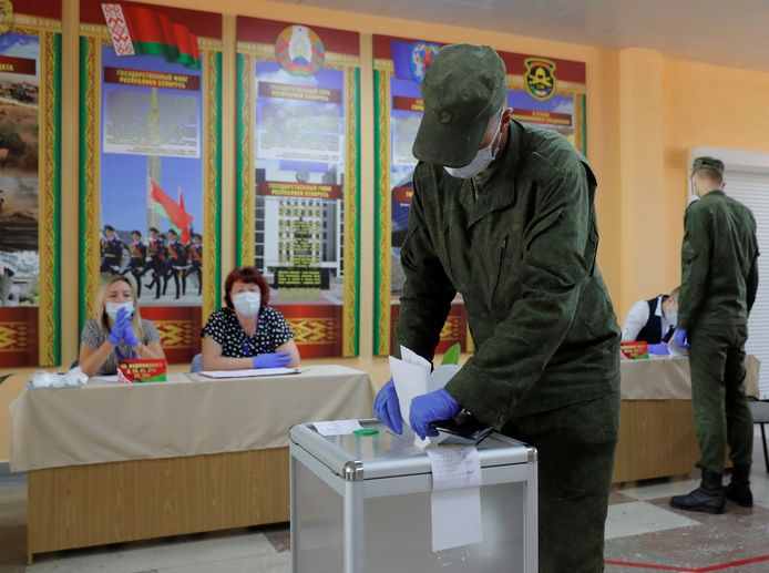 Een Wit-Russische soldaat  tijdens het uitbrengen van zijn stem in een stembureau in Minsk.
