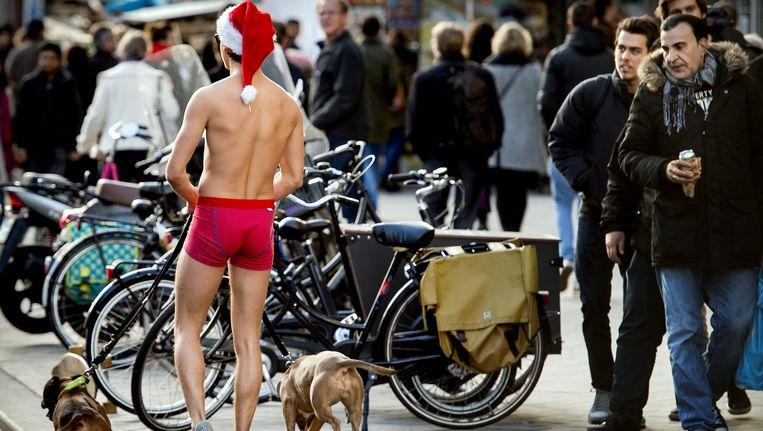 Een man met een kerstmuts laat zijn honden uit op het Rokin. Beeld anp