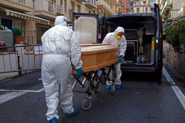 Medische staf brengt het lichaam van Assunta Pastore (87) weg. Nadat ze is gestorven aan het coronavirus in haar kamer in het Garden hotel in Laigueglia. Beeld AP