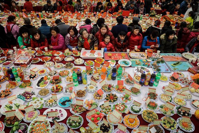Chinese buurtbewoners in Wuhan zitten rond grote tafels waarop huisgemaakte gerechten staan uitgestald. De wijkbewoners koken bij het begin van het nieuwe jaar duizenden gerechten en nodigen de buren uit om te proeven en te leren van de kookvaardigheden van anderen. Foto Wang He