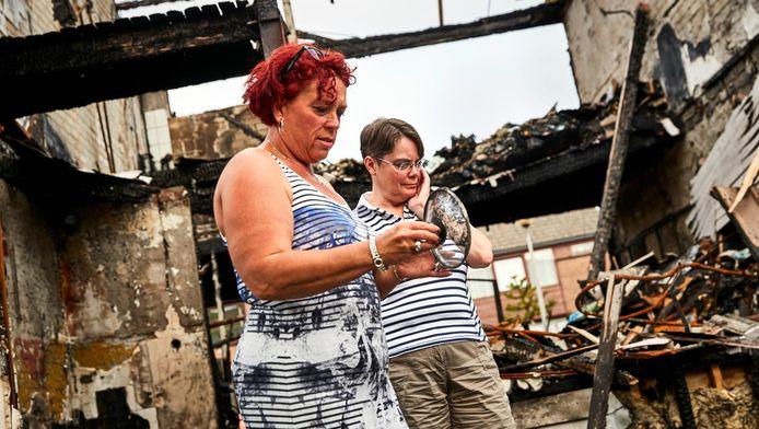 Dochters Margaret en Rianne Lampers op de resten van hun ouderlijk huis. Ouders Bram en Lucia waren kansloos in de vlammen.