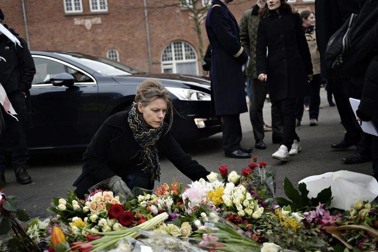Een vrouw legt bloemen bij de synagoge in Kopenhagen waar bij een aanslag een bewaker is gedood. Beeld epa