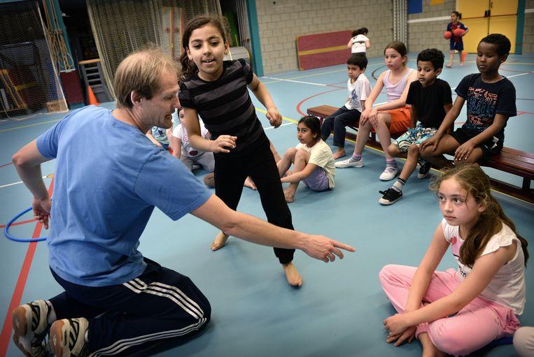 Een gymdocent geeft leerlingen instructies tijdens de gymles.  Beeld Marcel van den Bergh