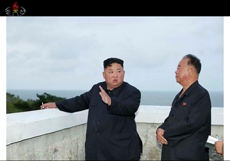 De Noord-Koreaanse leider Kim Jong-un (l) kijkt naar het testen van een nieuw wapensysteem.   Beeld AP