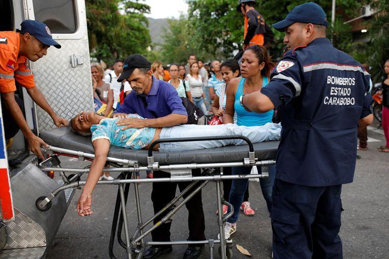 Paramedici helpen een flauwgevallen familielid van een van de gevangenen.