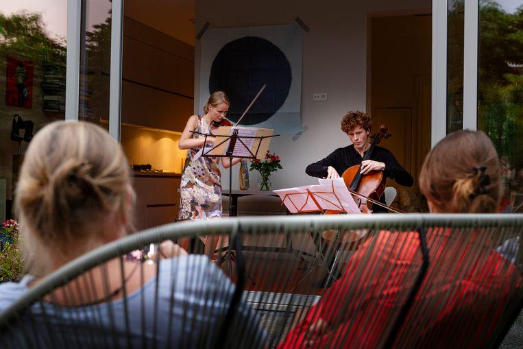 Violist Ruña 't Hart en cellist Kalle de Bie geven een tuinconcert in Amsterdam-Oost. Beeld Pauline Marie Niks