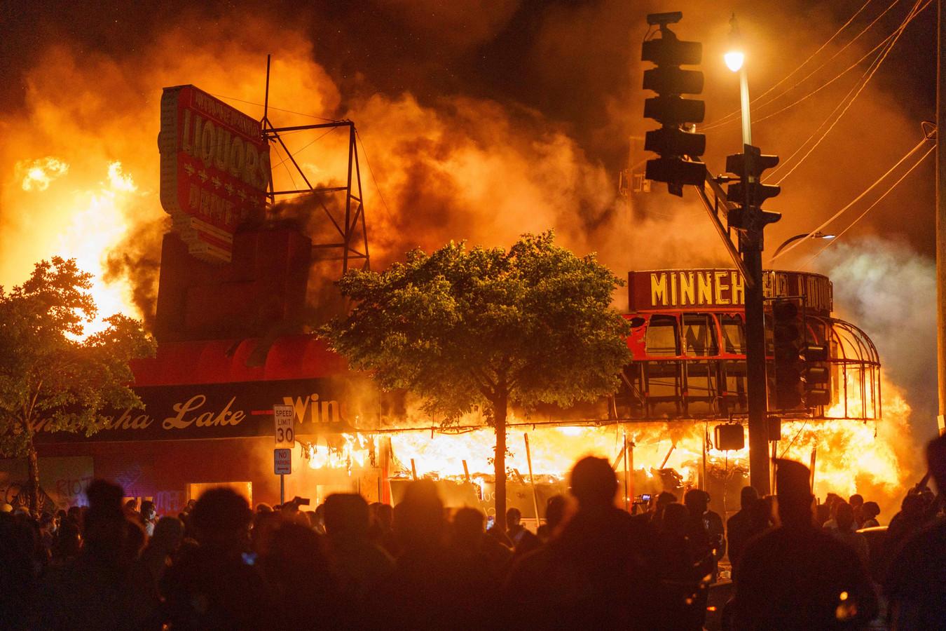 Demonstranten verzamelen zich voor een in brand gestoken slijterij bij het hoofdbureau voor politiepatrouilles en onderzoek in Minneapolis dat later in vlammen op zou gaan.