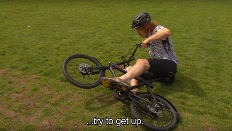 Fietsinstructeur Maxim Hartman demonstreert hoe je op de fiets kunt stappen. Beeld Screenshot Youtube