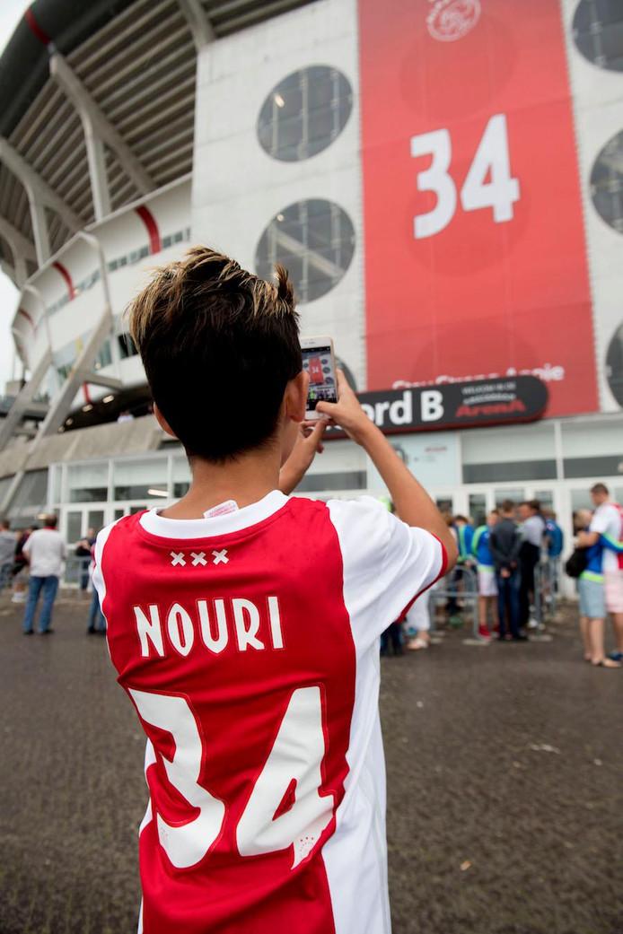 Een fan van Ajax maakt een foto van een groot spandoek met nummer 34,  het rugnummer van Abdelhak Nouri.