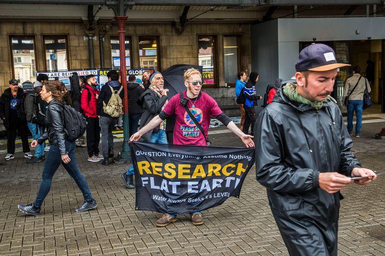 Mensen die geloven dat de aarde plat is kwamen dit weekend samen in Amsterdam. Op het centraal station in Amsterdam delen ze flyers uit. Beeld Arie Kievit