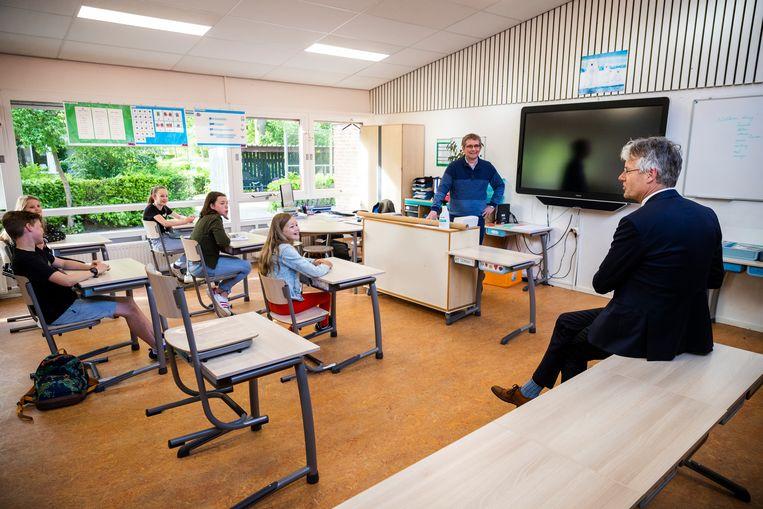 Minister Slob op bezoek bij een basisschool in april, waar de eerste lessen weer gegeven werden na een wekenlange onderbreking vanwege het coronavirus.  Beeld Jiri Büller