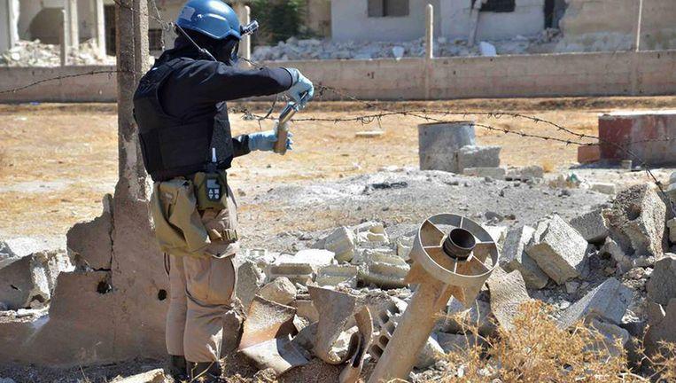 Een medewerker van de Verenigde Naties neemt proeven van de aarde in een gebied waar wellicht chemische wapens zijn gebruikt. Beeld ap