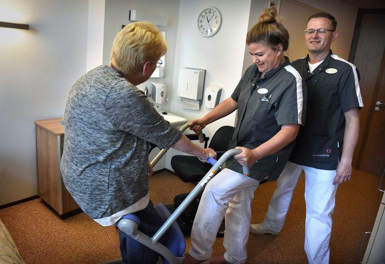 Verpleegkundigen helpen een patiënt in revalidatiecentrum Parkgraaf in Utrecht. Beeld Marcel van den Bergh / de Volkskrant