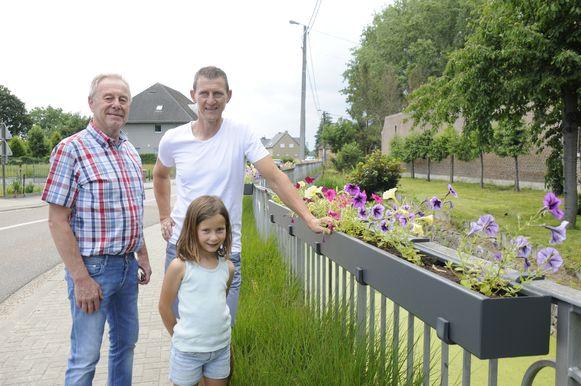 Schepen Paul Mathues en zijn opvolger Raf Lambeets samen met diens dochter aan de bloemenkorven.