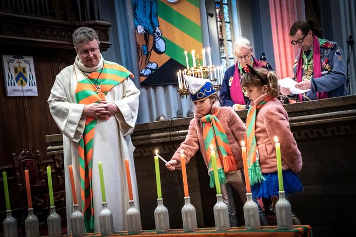 Diaken Geert Eijsbouts ziet toe hoe de kinderen van prins Knet 11 kaarsjes aansteken tijdens de Kruikenviering in de Heuvelse kerk.