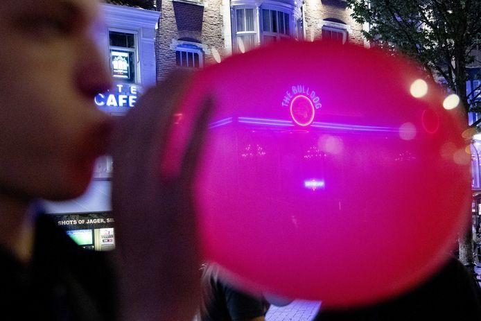 Foto ter illustratie. Een man zet een met lachgas gevulde ballon aan zijn mond in het centrum van Amsterdam.
