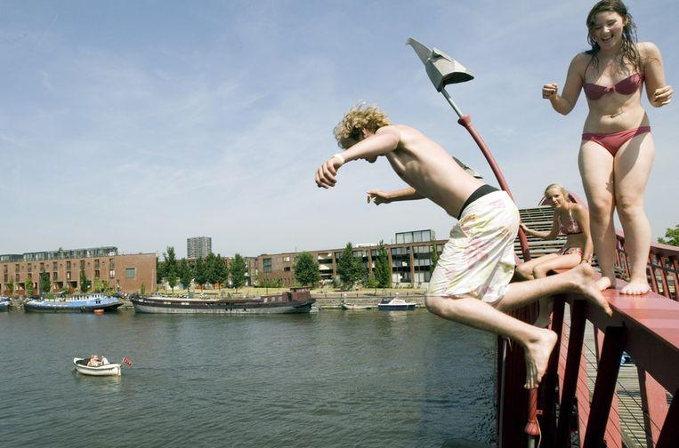 Jongeren springen van een brug in Amsterdam tijdens mooie, warme dagen eind juni/begin juli vorig jaar. © ANP Beeld