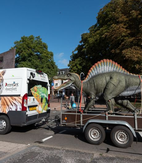 Spinosaurus op aanhanger trekt de aandacht op de weg