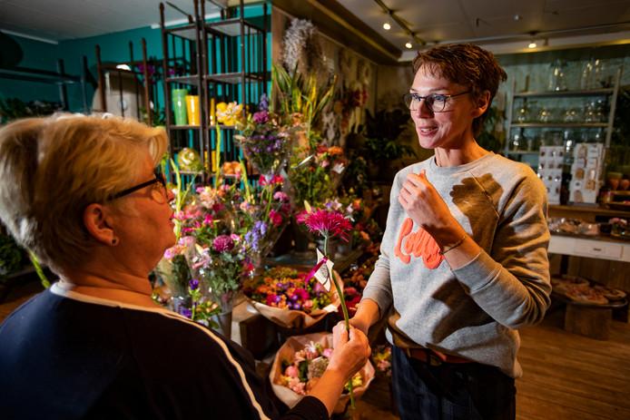 Ingrid van Eijk-Elshof, eigenaar van bloemenzaak Fleurissant, geeft bloemen weg in het kader van de maand van borstkanker.