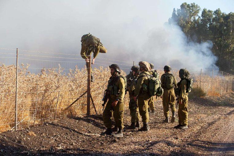 Israëlische soldaten inspecteren de plaats waar raketten vanuit Syrië neerkwamen.