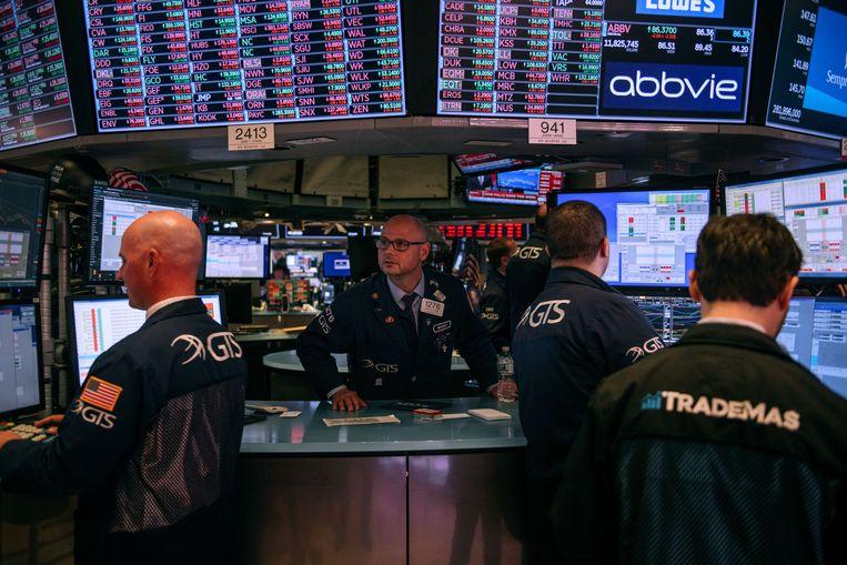 Handelaren op de beurs in New York. Als gevolg van de onrust over de economische gevolgen van het coronavirus daalden de koersen voor de vierde dag op rij. De Dow Jones-index daalde donderdag met bijna 1.200 punten.  Beeld AFP