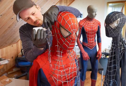 Yuri Schuurkes lijmt het web op het pak van Spider-Man. Rechts de outfit van de donkere tegenhanger.