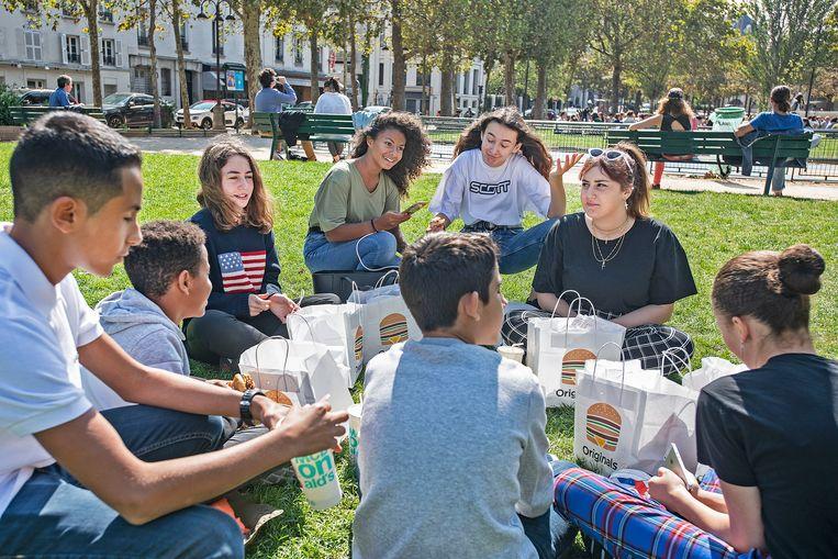Franse jeugd geniet van een middag lunch in een park. De Franse regering heeft het gebruik van mobiele telefoons op school geheel verboden. Beeld Guus Dubbelman / De Volkskrant