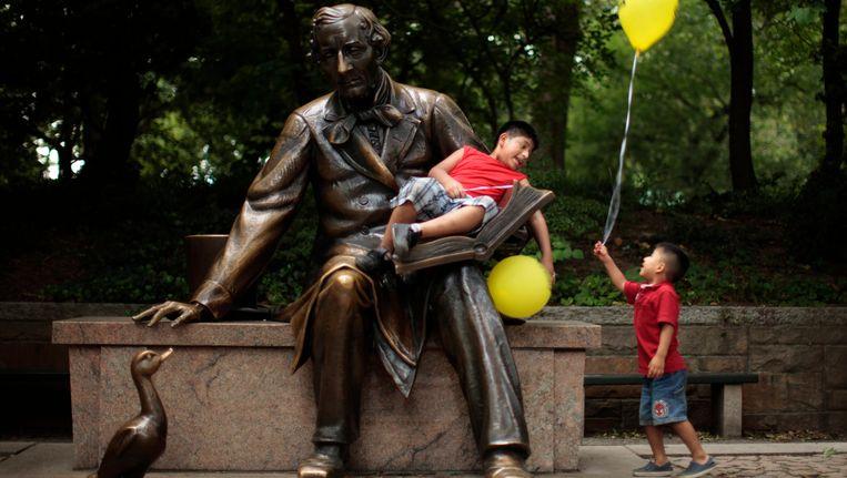 Twee kinderen spelen bij het standbeeld van Hans Christian Andersen in New York. Beeld REUTERS