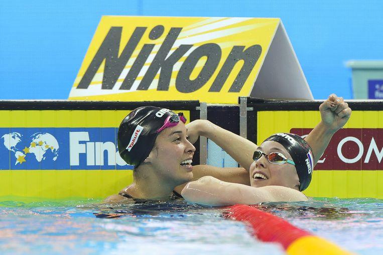 Ranomi Kromowidjojo (links) viert het winnen van de gouden plak op de 100 meter vrij. Femke Heemskerk (rechts) werd tweede. Beeld Getty Images